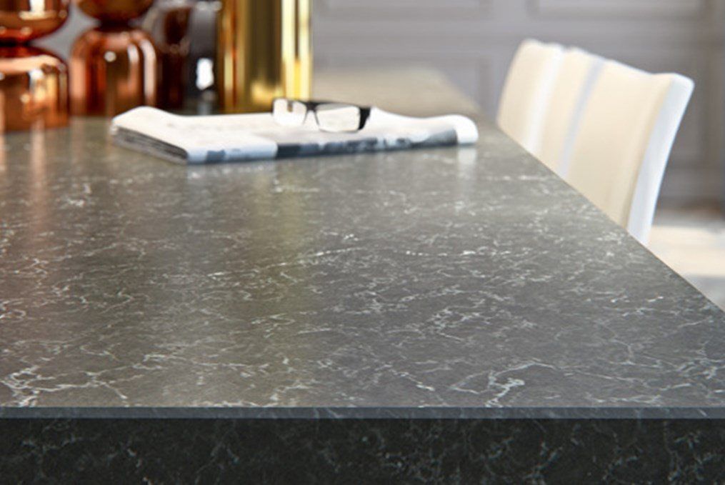 black granite counter with newspaper and glasses