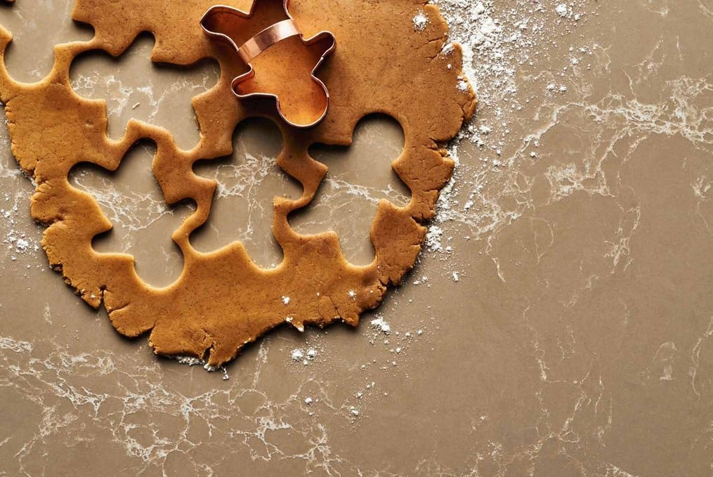 brown counter with cookie dough being cut into gingerbread men