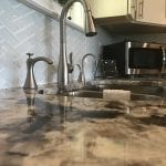 kitchen with black and ivory marbled counters and white cabinets